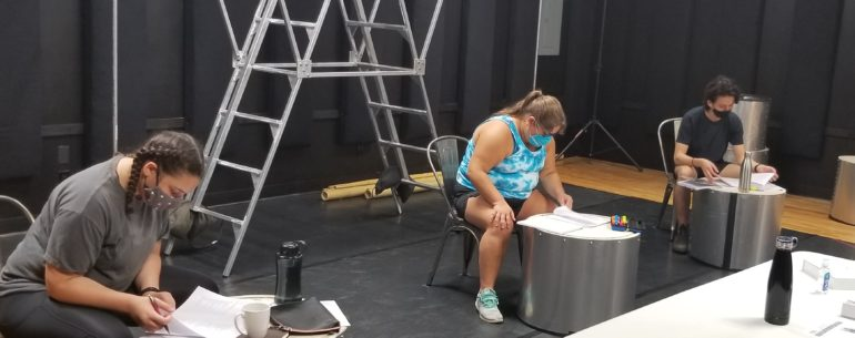 Three actors in a rehearsal studio. They are wearing masks and sitting on chairs in a line, 2 meters away from one another. They each have a small round table in front of them. They are looking down and reading from scripts placed on the tables. Behind them there is a metal ladder.