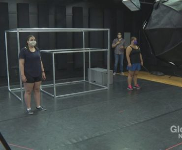 2 actors and a director in a rehearsal studio. The actors are facing forward and standing 2 meters away from each other. The director is watching from behind them. Between the actors, there are 2 large set pieces made up of metal rods that form a cube. There are cameras and lighting equipment around the room.