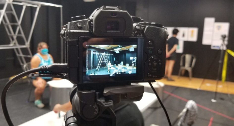 There is a video camera in the middle. We see a rehearsal studio on the camera screen, as well as around the camera. In the rehearsal studio, there is an actor sitting on a chair behind a small table, and another actor looking at costume sketches on a wall.